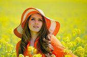 beautiful woman on blooming rapeseed field in summer