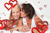 Man kissing his girlfriend on the cheek against love heart pattern