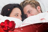 Couple under the duvet looking at each other against valentines heart design