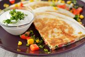 Vegetarian quesadilla with sour cream. Selective focus on the front wedge