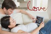 Prospective parents looking at ultrasound scan on tablet pc against love spelled out in petals