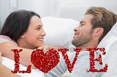 Cheerful couple awaking and looking at each other against love spelled out in petals