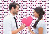 Pretty brunette giving boyfriend her heart against valentines day pattern