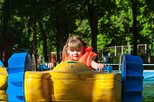 picture of life-boat  - little girl in a life jacket floats on the a boat - JPG