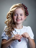 Laughing freckled girl posing with cherries