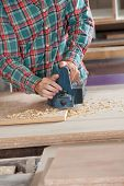 Midsection of worker using electric planer on wood at workshop