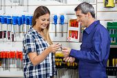 Side view of smiling male vendor giving wrench to female customer in hardware shop