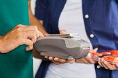 Worker accepting payment through smartphone with customer holding screwdriver set in store