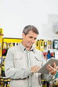 Mature man using tablet computer in hardware store