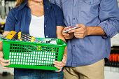 Midsection of couple carrying basket full of tools in hardware store
