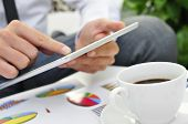 closeup of a young businessman using a tablet on a table full of charts