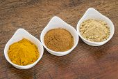 three healthy spices (turmeric, ginger and cinnamon) in white bowls on a grunge wood