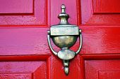 brass knocker on a bright red door