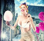 stock photo of candy cotton  - Beautiful crazy girl riding rotifers holding sweet candy cotton - JPG