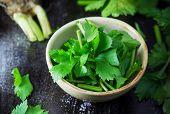 stock photo of ceramic bowl  - fresh celery in ceramic bowl on wooden background  - JPG