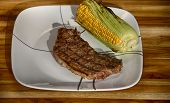 foto of peppercorns  - Choice cut of steak seasoned with Himalayan salt and peppercorn alongside a half corn on the cob still in the husk plated on white dinnerware on a teak cutting board - JPG