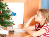 image of letters to santa claus  - little girl writes a letter to Santa Claus sitting at a desk - JPG