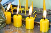 picture of candle flame  - Close up yellow candles with flame in temple - JPG