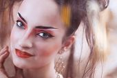 picture of geisha  - Close up stylized portrait of a Japanese geisha with bright make up standing at the window watching the rain - JPG