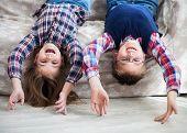 foto of upside  - Happy children upside down on the sofa - JPG