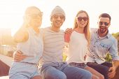 stock photo of bonding  - Four young cheerful people bonding to each other and smiling while sitting on the roof of the building together - JPG