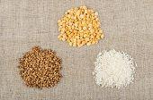 stock photo of buckwheat  - Three heap of dry rice buckwheat and peas on burlap - JPG