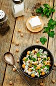picture of chickpea  - salad with chickpeas feta and parsley on a dark wood background