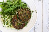 picture of veggie burger  - Swiss chard veggie fritters with mash potatoes and rocket leaves on white plate and white rough background copy splace - JPG