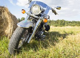 stock photo of haystacks  - Motorcycle in a field outside the city near a haystack