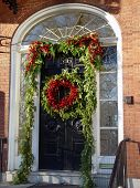 Christmas Wreath With Garland And Holly Berries On Door