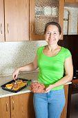 Woman Making Stuffed Vegetable Marrow  In Her Kitchen