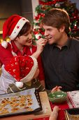 picture of nuclear family  - Smiling wife handing christmas cake to father to taste kid watching - JPG