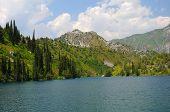 Lago colorido com montanhas, céu e nuvens