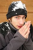 image of shivering  - Young man shivers rubbing his hands together in the snow - JPG