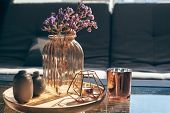Home interior decor in gray and brown colors: glass jar with dried flowers, vase and candle on the w poster