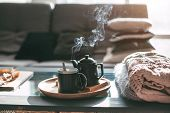 Still life details in home interior of living room. Sweaters and cup of tea with steam on a serving  poster