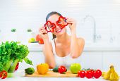 Beauty young funny woman holding fresh vegetables- peppers and smiling in her kitchen at home. Healt poster