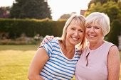 Senior woman and adult daughter embracing in garden poster