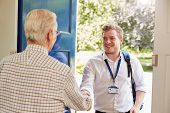 Senior man greeting male care worker making home visit poster