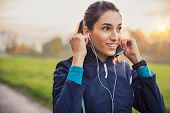 Young athlete adjusting jacket while listening to music at park. Smiling young woman feeling relaxed poster
