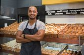 Smiling baker man standing with fresh bread at bakery. Happy african man standing with crossed arms  poster