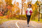Mature Asian woman running active in her 50s. Middle aged female jogging outdoor living healthy life poster