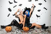 Two cheerful young women in leather halloween costumes posing with curved pumpkins over bats and con poster