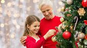 winter holidays, family and people concept - happy grandmother and granddaughter decorating christma poster