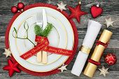 Christmas table place setting with dinner plates, cutlery with fir and ribbon, napkin, cracker and b poster