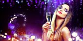 Sexy model girl with glass of champagne at party, drinking champagne over holiday glowing blue backg poster