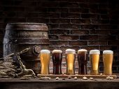 Glasses of beer and ale barrel on the wooden table. Craft brewery. Beer background. poster