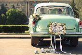 Wedding couple in car decorated with plate JUST MARRIED and cans outdoors poster