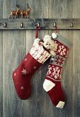 Pair of Christmas stockings hanging from hooks with reindeer figures sitting on the ledge poster