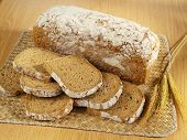 stock photo of whole-grain  - Freshly baked bread and wheat on table - JPG